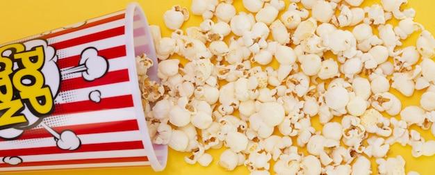 Boterpopcorn in een rode popcornkop, snack in huis of bioscoop