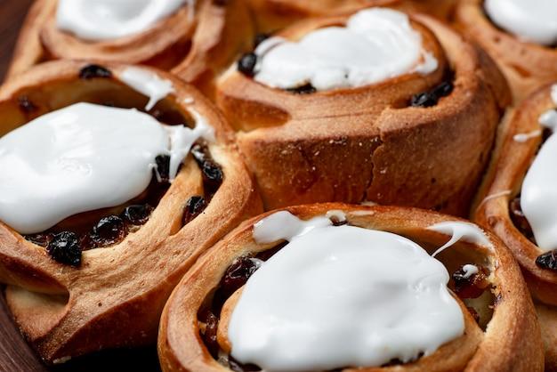 Boterzoete broodjes met rozijnen. afgedekt met witte suikersiroop.