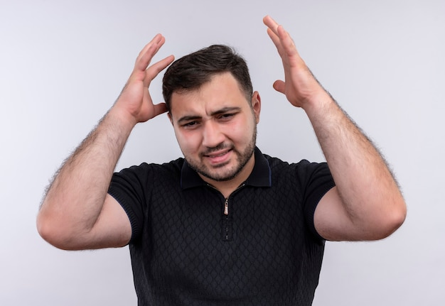 Bothred jonge, bebaarde man in zwart overhemd armen met geïrriteerde uitdrukking opheffen