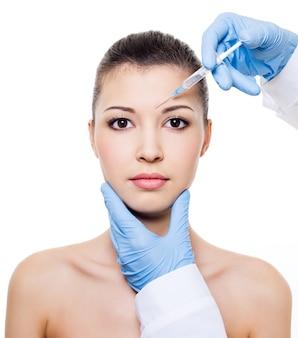 Botox-injectie in de wenkbrauw op vrouwelijk gezicht dat op wit wordt geïsoleerd