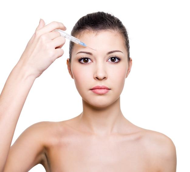Botox-injectie in voorhoofd voor de mooie jonge vrouw die op wit wordt geïsoleerd