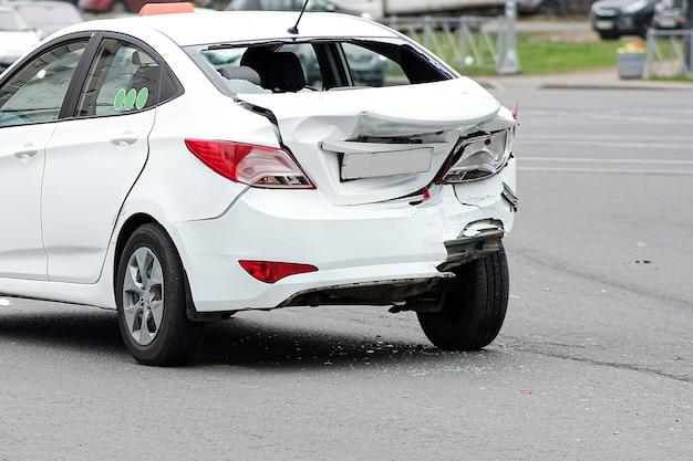 Botsing van auto's. de witte taxi-auto liep ernstige schade op aan de achterzijde van het lichaam. gebroken bumper en kofferdeksel.
