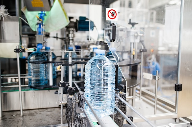 Bottelinstallatie - waterbottellijn voor het verwerken en bottelen van zuiver bronwater in blauwe flessen. selectieve aandacht.