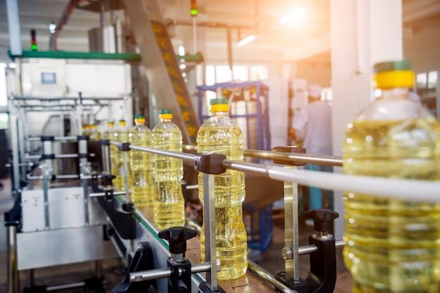 Bottellijn van zonnebloemolie in flessen. plantaardige plantaardige productie-installatie.