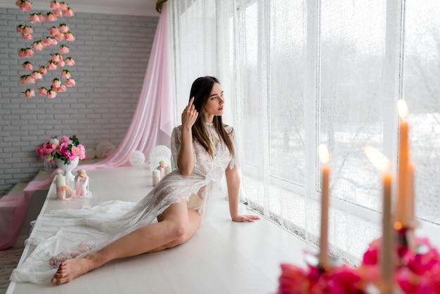 Boudoir ochtend van de bruid. bruid blijft bij het raam