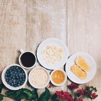 Bougainvilleabloemen met ontbijt en koffie op plank