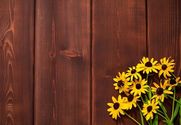Bouguet van gele bloemen in hoek op houten achtergrond