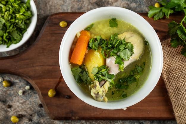 Bouillon soep met wortel, aardappel en gehakt groen