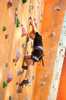 Boulderen, klein meisje dat tegen de muur klimt