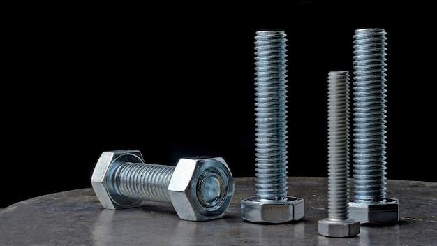 Bouten en zeskantmoeren van verschillende afmetingen, neergelegd op een metalen oppervlak. diverse close-ups.