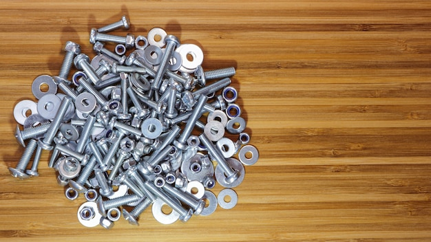 Bouten, moeren en ringen van verschillende afmetingen en houten bamboe tafelblad. kopieer ruimte voor tekst.