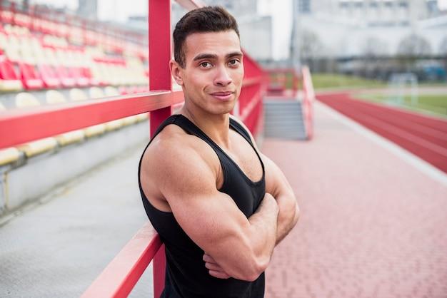 Bouw atleet op met zijn arm gekruist op stadionspoor en veld