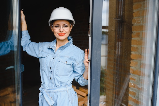 Bouw concept. vrij vrouwelijke bouwer in overall en helm die op bouwplaats werken.