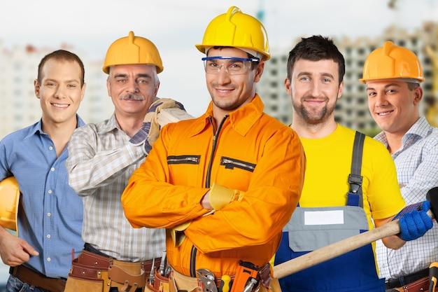 Bouw, constructie, ontwikkeling, teamwork en mensenconcept - groep bouwers in veiligheidshelmen