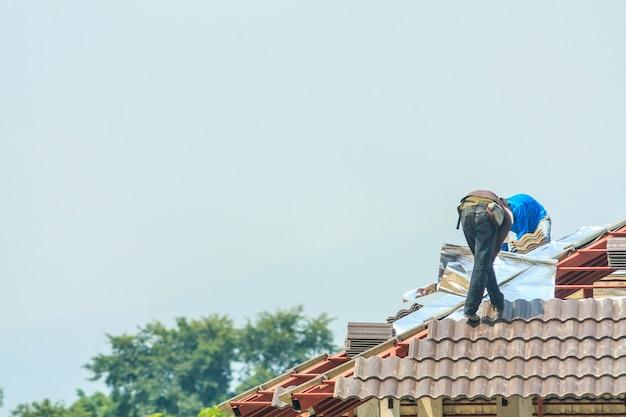 Bouw dakdekker die dakpannen installeert op de bouwplaats van een huis