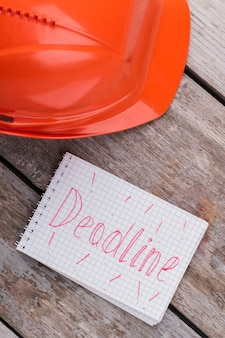 Bouw deadline concept. oranje arbeidershelm op een vintage oude houten tafel.