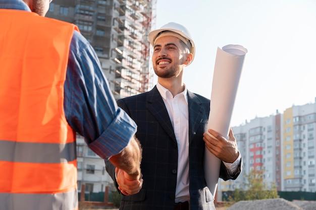 Bouw- en bouwvakker op de site met architect