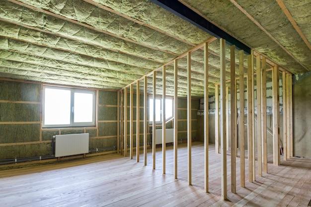 Bouw en renovatie van grote lichte ruime lege ruimte met eiken vloer, wanden en plafond geïsoleerd met steenwol, verwarmingsradiatoren onder lage zolderramen en houten frame voor toekomstige muren.