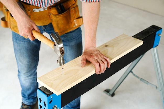 Bouw en reparatie. timmerwerk. werknemer hamers een spijker