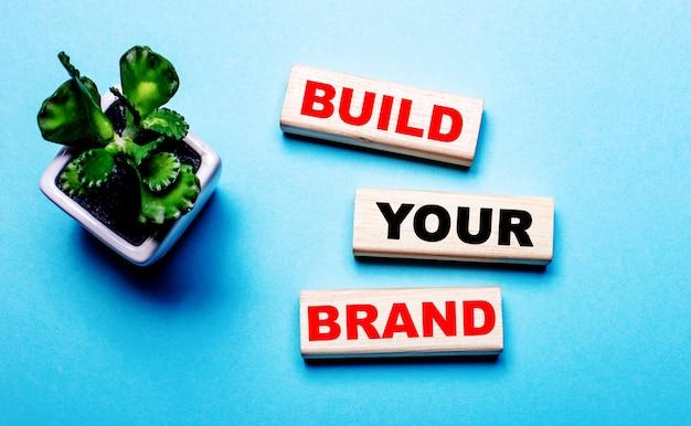 Bouw je merk houten blokken op een lichtblauwe achtergrond bij een bloem in een pot