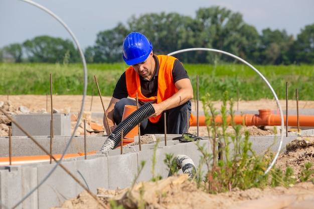 Bouw- of werfleider die de funderingen van het nieuwe huis, gebouw of constructie controleert of overziet