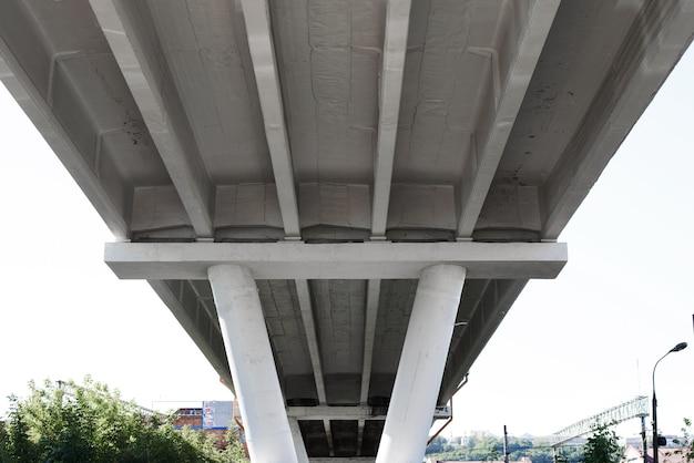 Bouw van een betonnen verkeersbrug ondersteund door pilaren, van onder naar boven gezien. onder de brug, perspectief
