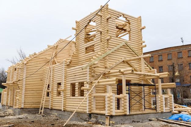Bouw van een christelijke kerk gemaakt van met hout behandelde stammen met de hand zonder spijkers