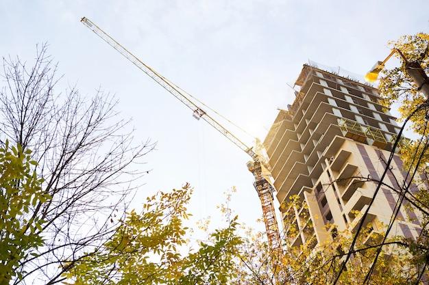 Bouw van een flatgebouw met meerdere verdiepingen in de stad. een kraan in de buurt van een wolkenkrabber. bouwen, verhuizen naar een nieuwe flat, hypotheek, huur en aankoop onroerend goed. ruimte kopiëren