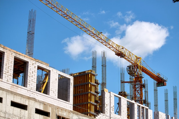 Bouw van een hoogbouw, de vorming van cementsteunen en de werking van een kraan tegen een blauwe hemel, selectieve aandacht
