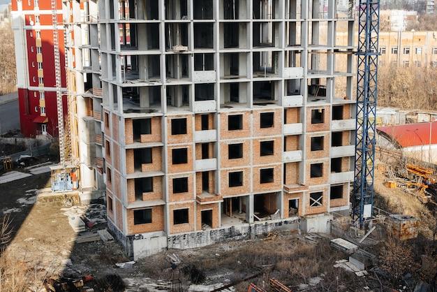 Bouw van een moderne hoogbouwwolkenkrabber met kranen in het centrum van de metropool