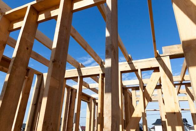Bouw van een nieuw framehuis, waar het frame van houten planken wordt gemonteerd, close-up vanuit het midden van het gebouw