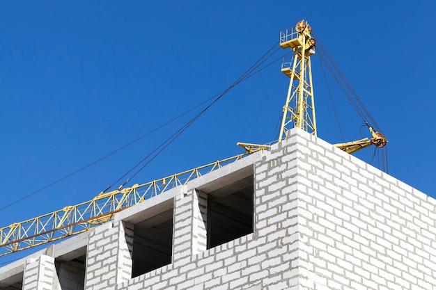 Bouw van een nieuwe hoogbouw van gassilicaatblokken en bakstenen, een bouwplaats met bouwkranen