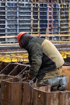 Bouw van een woonhuis waarbij metalen constructies worden gelast voor de bouw van een monolithische