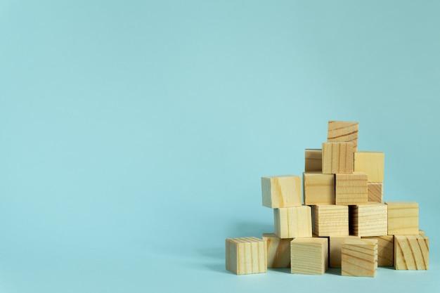 Bouw van houten kubussen op blauwe achtergrond met exemplaarruimte. mockupsamenstelling voor ontwerp