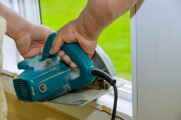 Bouw verbouwing huis snijden houten sierplank op met handcirkelzaag.