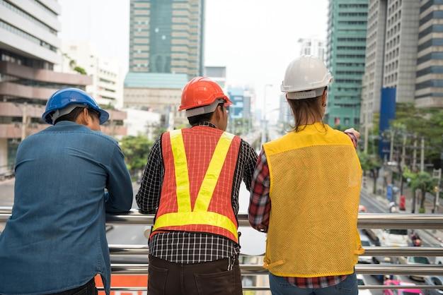 Bouw vrouwelijke ingenieur staan op het centrum van de wolkenkrabber haar vinger op renoveren bouwgebouw in de moderne stad. achterteam van diverse professionele racearbeiders in vest en helm.