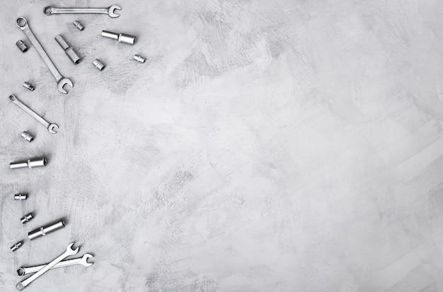 Bouwachtergrond van grijze kleur met handgereedschap voor reparatie op het bovenaanzicht