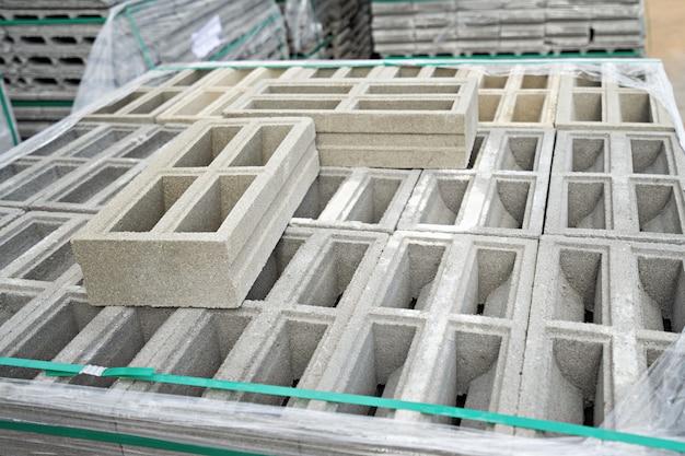 Bouwconcept, baksteenblokken op pallets in het magazijn.