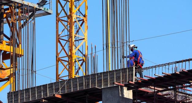 Bouwconstructieplaats en werknemer permanent op staal en beton materiaal en blauwe hemel.