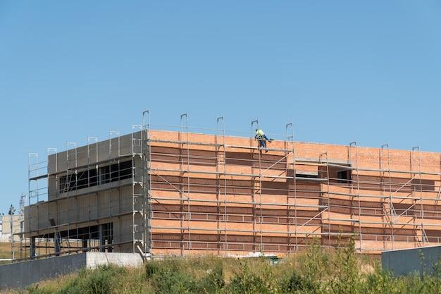 Bouwconstructieplaats met steigers en onherkenbare arbeider