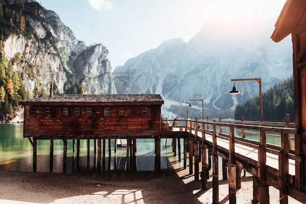 Bouwen aan het bruine huis en zijaanzicht ervan. goed landschap met bergen. toeristische plaats met houten gebouw en peer