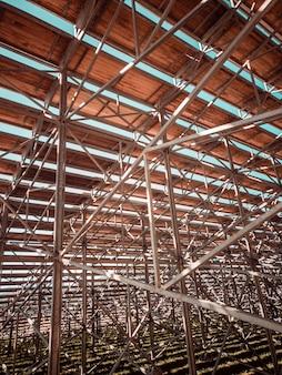 Bouwen met metalen staven en houten plafond