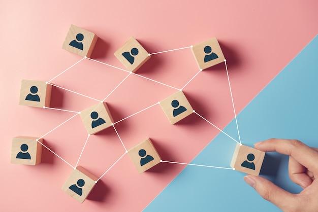 Bouwend een sterk team, houten blokken met mensenpictogram op blauwe en roze achtergrond, personeel en beheersconcept.