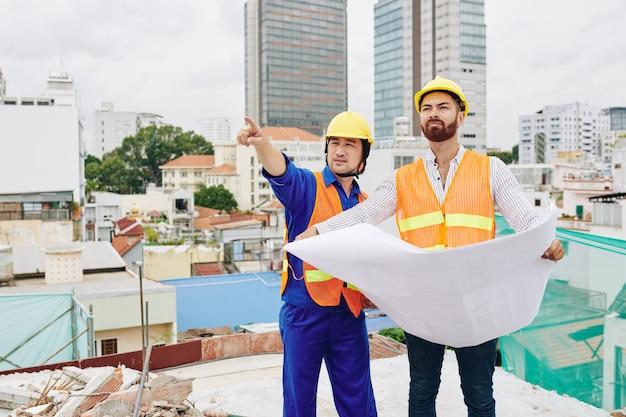 Bouwer afgewerkte muur tonen aan aannemer met blauwdruk in handen bouwen