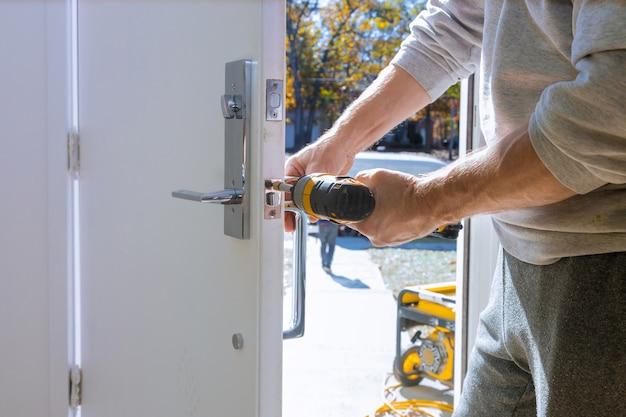 Bouwer bij het installeren van een deurslot de deur van een nieuw huis