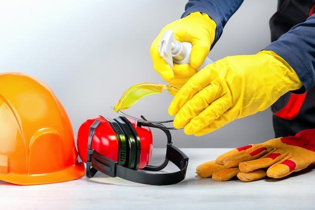 Bouwer die beschermende kleding op de werkplek desinfecteert.