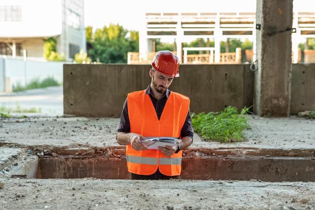 Bouwer die documenten op bouwwerf bekijkt