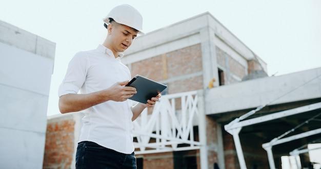 Bouwer die in een tablet kijkt terwijl hij het toekomstige bouwplan maakt terwijl hij een helm draagt