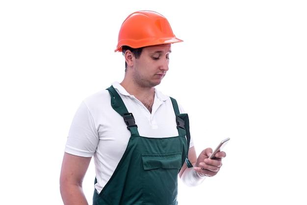 Bouwer die in overall mobiele telefoon houdt die op witte muur wordt geïsoleerd