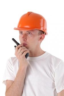 Bouwer die op draagbare uhf-radiozendontvanger spreekt die op wit wordt geïsoleerd